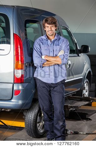 Confident Mechanic Standing Arms Crossed By Car