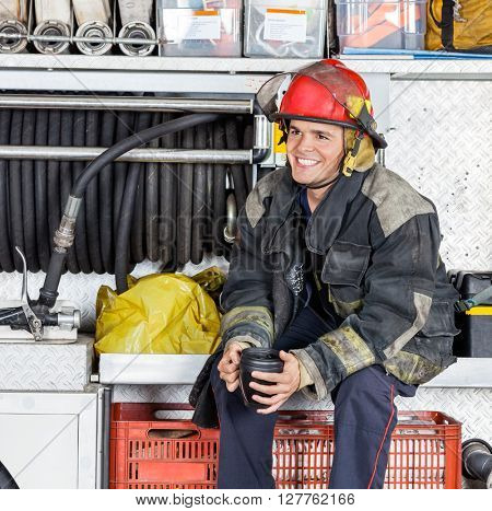 Happy Fireman Holding Coffee Mug In Truck At Fire Station