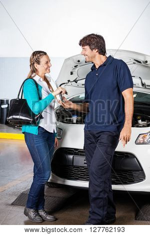 Customer Giving Car Keys To Technician At Garage