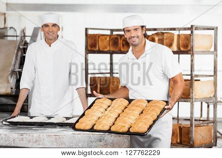 Baker Showing Breads In Baking Tray By Colleague