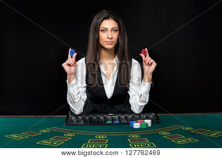 The beautiful girl, dealer, behind a table for game in poker. the dealer deals the cards.