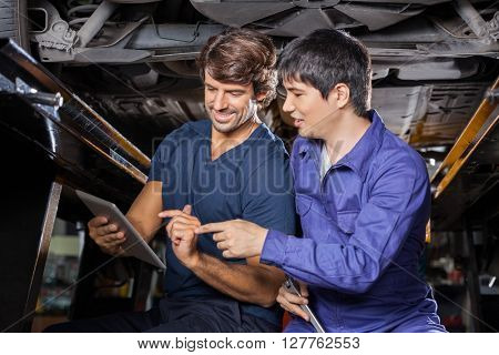 Mechanics Using Tablet Computer Under Lifted Car