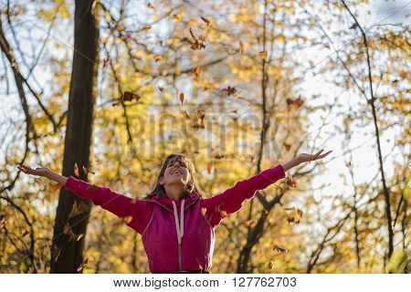 Happy young woman in pink jacket throwing leaves in the air standing in autumn forest with arms outstretched.
