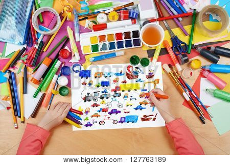 cartoon game toy and people collection child drawing , top view hands with pencil painting picture on paper, artwork workplace