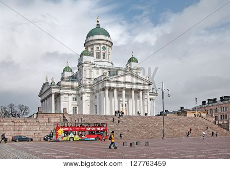 HELSINKI, FINLAND - APRIL 23, 2016: Hop-On Hop-Off  - City Tour Bus on The Senate Square near Helsinki Cathedral. Traveling In the bus can see the best sights and listen to the excursion in ten languages