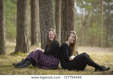 Teenage girls best friends sitting in the forest and laughing.