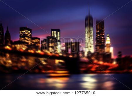 Abstract blurred Brooklyn Bridge East River and Manhattan at night with lights and reflections. New York City