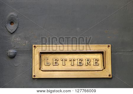 Details of an old Italian letter box on wooden door in Italy