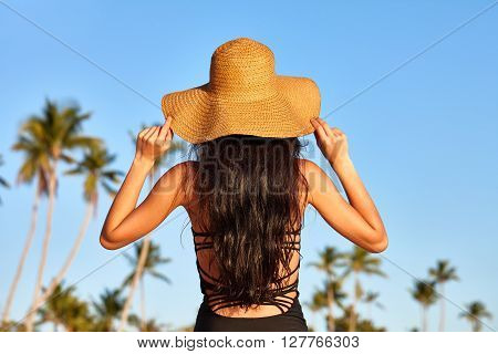 Beach vacation. A beautiful woman in a sunhat standing on a blue sky and palms background.