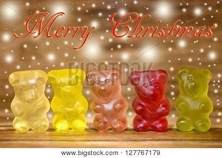 multicolored candy bears and glitter on wood and merry christmas written