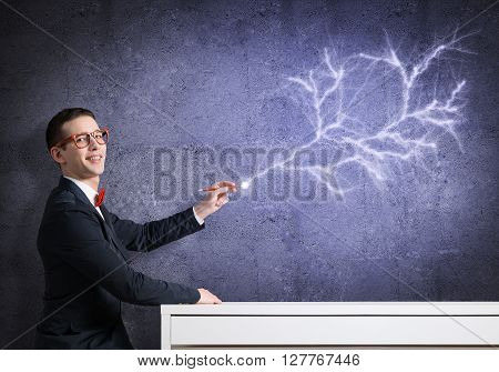 Handsome student sitting at table and drawing on concrete wall