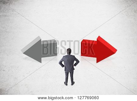 Different direction concept with businessman and two arrows on concrete background
