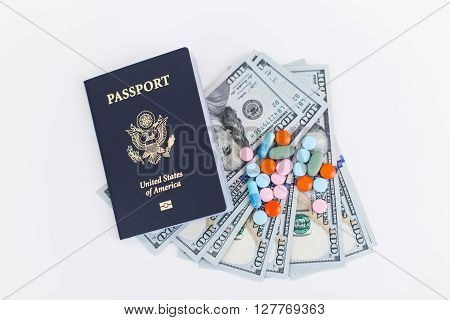 Topview of american passport dollars and pills on white surface. Concept of going abroad for medical treatment
