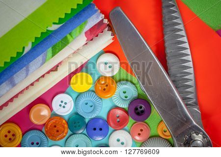 background with sewing accessories, with colored chintz, buttons, serrated shears, set for needlework