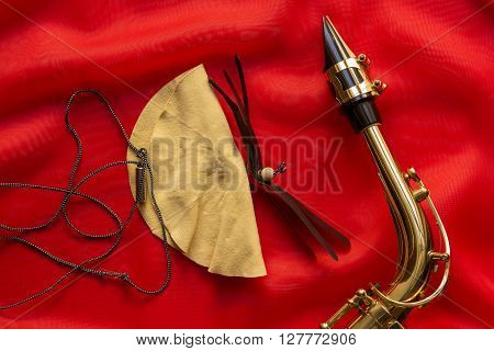 Suede brush and saxophone mouthpiece on a red background