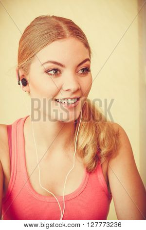 Young woman with earphones listening to music. Girl relaxing enjoying. People relax leisure pleasure concept.