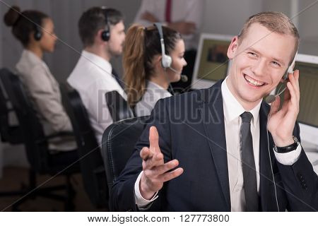 Shot of a young telemarketer laughing talking and with his client