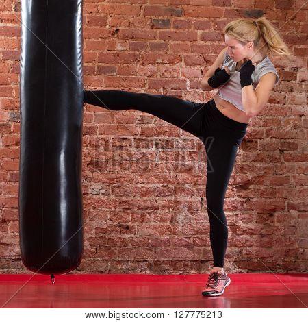 Girl Kicking At Punching Bag