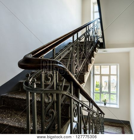 Staircase with old decorative railing and white walls