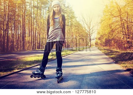Teenage girl on roller skates at summer. Inline skates sport conceptual image. Instagram vintage picture.