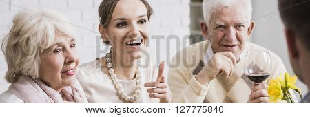 Young woman and her older parents during family dinner joking and having fun together