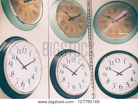 Clocks hanging on wall. Abstract background with vintage filtered.