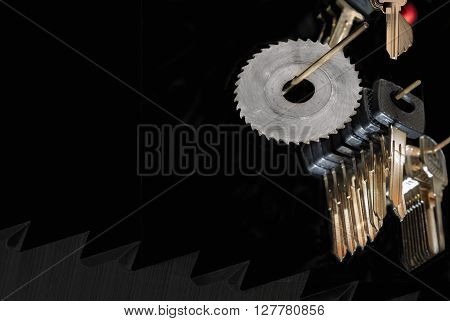 Blank car keys and milling cutter saw on a black background with red accent