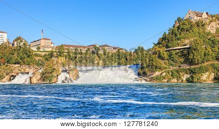 The Rhine Falls in summer. The Rhine Falls (Rheinfall in German) is the largest plain waterfall in Europe located on the Rhine river in Switzerland.
