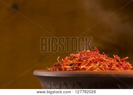 Saffron spices in clay pots on a wooden background