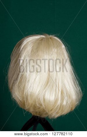 Artificial wig with white hair on a green background