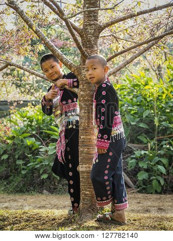 CHIANG MAI THAILAND - JANUARY 26 2015: Hill tribes child under the tree. Hmong new year festival day.