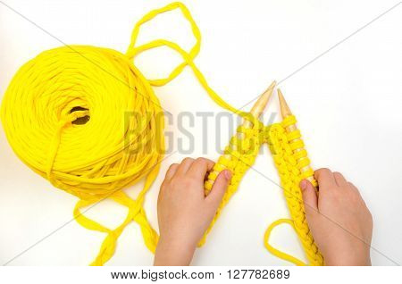 little girl knits large bamboo needles of a thick fabric yarn