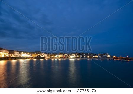 Scenic view of St Ives Cornwall UK at night with the lights reflected in the calm water of the bay under a twilight blue sky