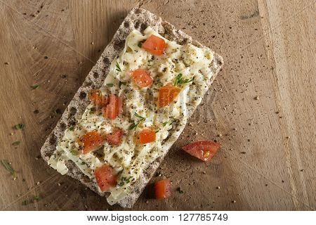 Crispbread with cheese tomato and spices on wooden background. Healthy breakfast.