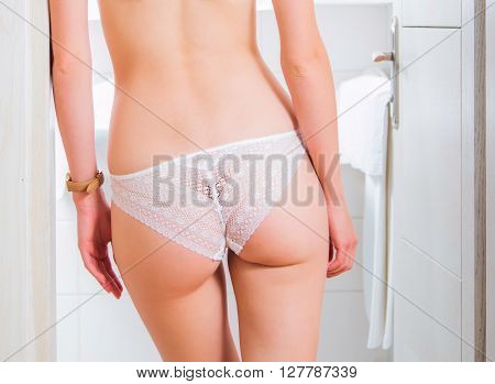Sexy girl in white lace underwear standing on bathroom door, butt, body detail, no face, anonymous