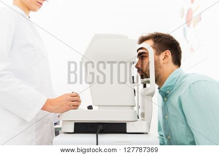 health care, medicine, people, eyesight and technology concept - close up of optometrist with autorefractor checking patient vision at eye clinic or optics store