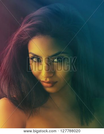 Beautiful exotic young woman - image captured in dark moody lighting with color gels