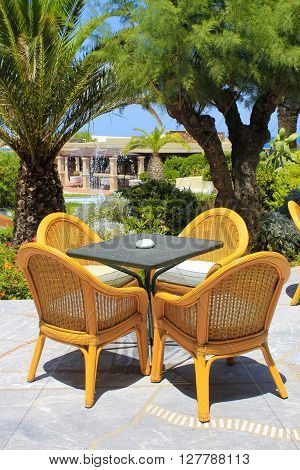 Al fresco terrace wicker chairs and palm trees in the mediterranean hotel, Crete, Greece