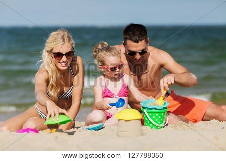 family, travel, vacation and people concept - happy man, woman and little girl in sunglasses playing with sand toys on summer beach