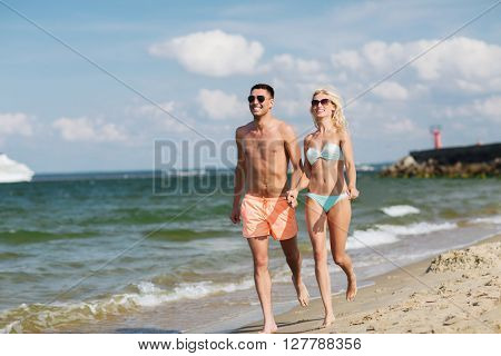love, travel, tourism, summer and people concept - smiling couple on vacation in swimwear and sunglasses holding hands and running on beach