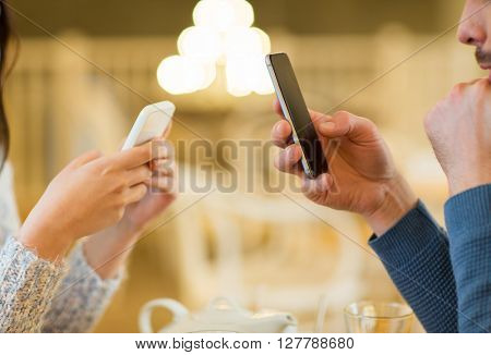 people, communication and technology concept - close up of couple with smartphones drinking tea at cafe or restaurant
