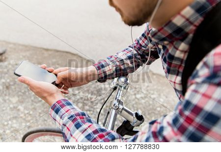 people, style, technology, leisure and lifestyle - close up of young hipster man in earphones with smartphone and fixed gear bike listening to music on city street