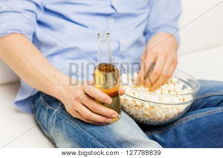 food, junk-food, unhealthy eating and people concept - close up of man with popcorn and beer bottle at home