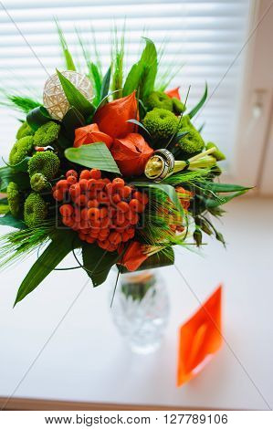 Unusual wedding bouquet with two wedding ring. Bouquet of physalis rowan ear of wheat in a glass vase on the white windowsill. Paper Boat next to a vase.