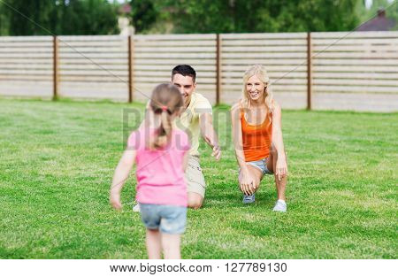family, happiness, adoption and people concept - happy little girl running towards father and mother outdoors