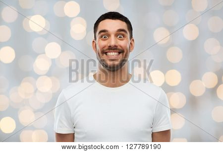 expression, emotions and people concept - man with funny face over holidays lights background