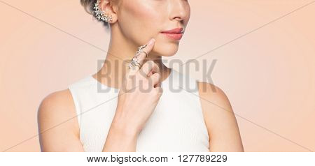 glamour, beauty, jewelry and luxury concept - close up of beautiful woman with golden ring and diamond earring over beige background
