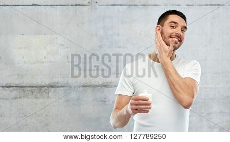 beauty, skin care, body care and people concept - smiling young man applying cream or lotion to face over gray wall background