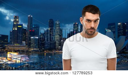 travel, tourism, people concept - young man portrait over night singapore city background