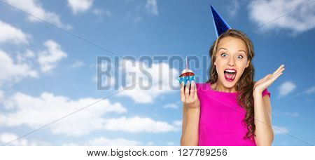 people, holidays, emotion, expression and celebration concept - happy young woman or teen girl in pink dress and party cap with birthday cupcake over blue sky and clouds background